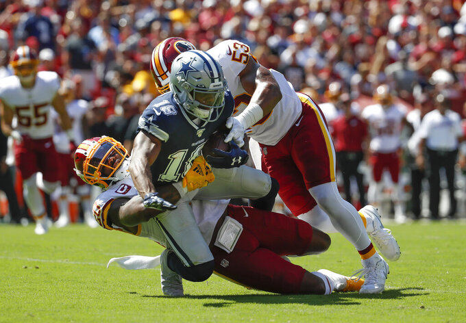 Dallas Cowboys wide receiver Randall Cobb (18) is stopped by Washington Redskins strong safety Landon Collins (20) and inside linebacker Jon Bostic (53) in the first half of an NFL football game, Sunday, Sept. 15, 2019, in Landover, Md. (AP Photo/Alex Brandon)