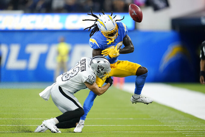Los Angeles Chargers receiver Tevaughn Campbell can't make the catch as he is hit by Las Vegas Raiders defender Hunter Renfrow during the first half of an NFL football game Monday, Oct. 4, 2021, in Inglewood, Calif. (AP Photo/Marcio Jose Sanchez)