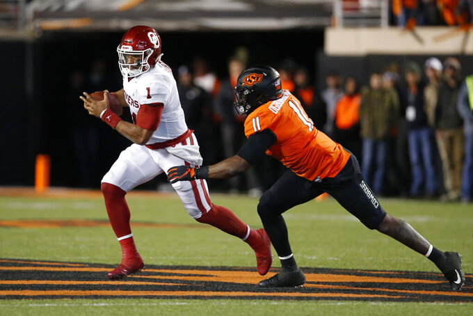 Oklahoma quarterback Jalen Hurts (1) is pursued by Oklahoma State linebacker Amen Ogbongbemiga (11) in the second half of an NCAA college football game in Stillwater, Okla., Saturday, Nov. 30, 2019. (AP Photo/Sue Ogrocki)