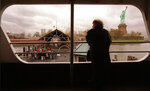 FILE - In this Nov. 14, 1995, file photo, Sonja Kuhnelt of Germany peers out a ferry window at the Statue of Liberty as a small group of visitors wait on the dock to board the vessel.  (AP Photo/Adam Nadel, File)