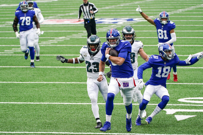 New York Giants' Daniel Jones (8) runs away from Philadelphia Eagles' Rodney McLeod (23) for a touchdown during the first half of an NFL football game Sunday, Nov. 15, 2020, in East Rutherford, N.J. (AP Photo/Seth Wenig)