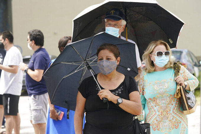 Angela Del Campo waits in line with others to get a COVID-19 rapid test, Monday, July 26, 2021, in Miami. More than 73,000 new coronavirus cases were reported in Florida over the previous week, according to the state health department, nearly seven times the 12,000 reported a month ago. (AP Photo/Marta Lavandier)