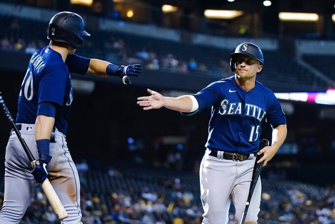 Seattle Mariners' Kyle Seager (15) celebrates his run scored against the Arizona Diamondbacks with teammate Jarred Kelenic (10) during the 11th inning of a baseball game Sunday, Sept. 5, 2021, in Phoenix. (AP Photo/Ross D. Franklin)