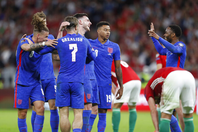 England's Declan Rice, center with number 4, celebrates with Kalvin Phillips, left, Jack Grealish, number 7, Jesse Lingard, number 19, and Raheem Sterling, right, after Rice scored his side's fourth goal during the World Cup 2022 group I qualifying soccer match between Hungary and England at the Ferenc Puskas stadium in Budapest, Hungary, Thursday, Sept. 2, 2021. (AP Photo/Laszlo Balogh)
