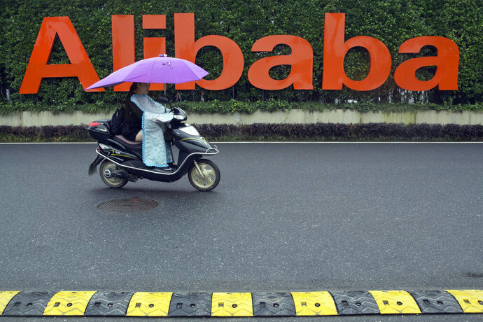 FILE - In this May 27, 2016, file photo, a woman rides a bike past the company logo outside the Alibaba Group headquarters in Hangzhou, in eastern China's Zhejiang province. The Chinese e-commerce giant Alibaba has raised about $11 billion in a share offering in Hong Kong, the city's biggest offering since 2010. Alibaba said Wednesday that it has set the price for the offering at 176 Hong Kong dollars ($22.50) per share. (AP Photo/Ng Han Guan, File)