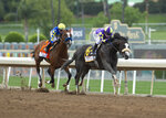 In a photo provided by Benoit Photo,C R K Stable's Honor A.P. and jockey Mike Smith, right, glide by Authentic and jockey Drayden Van Dyke in mid-stretch and to on to win the Grade I $400,000 RUNHAPPY Santa Anita Derby Saturday, June 6, 2020 at Santa Anita Park in Arcadia, Calif. (Benoit Photo via AP)