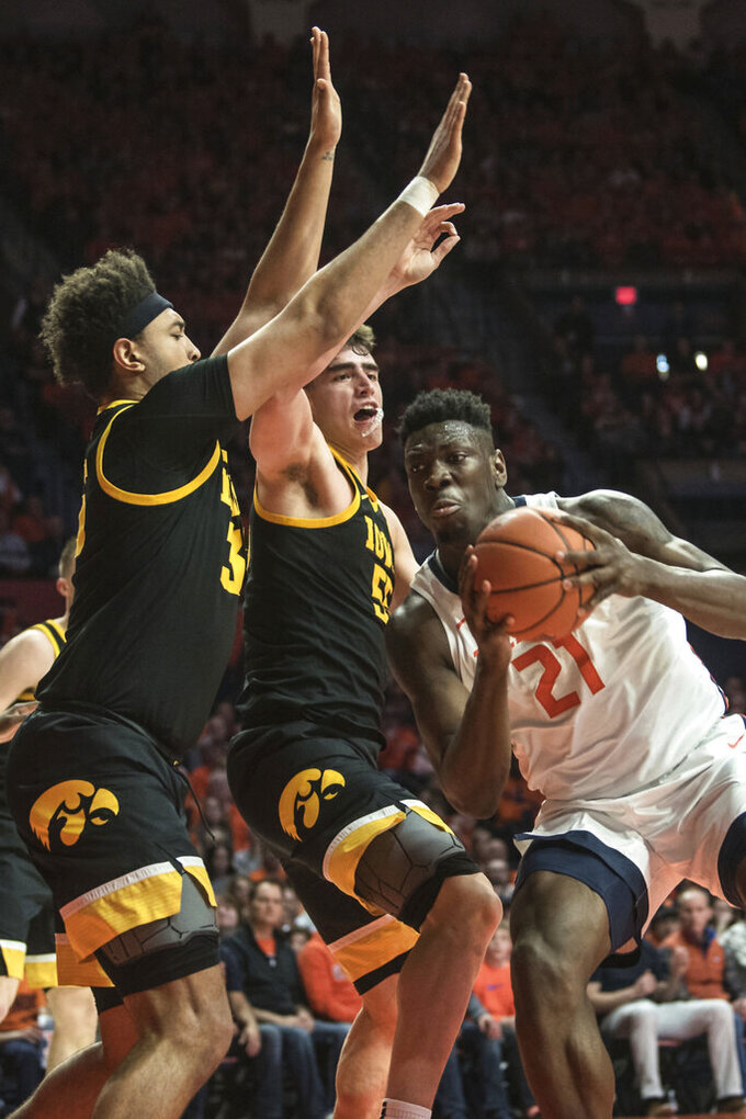 Illinois' Kofi Cockburn (21) powers to the basket as Iowa's Cordell Pemsl (35) and Luca Garza (55) defend in the first half of an NCAA college basketball game Sunday, March 8, 2020, in Champaign, Ill. (AP Photo/Holly Hart)