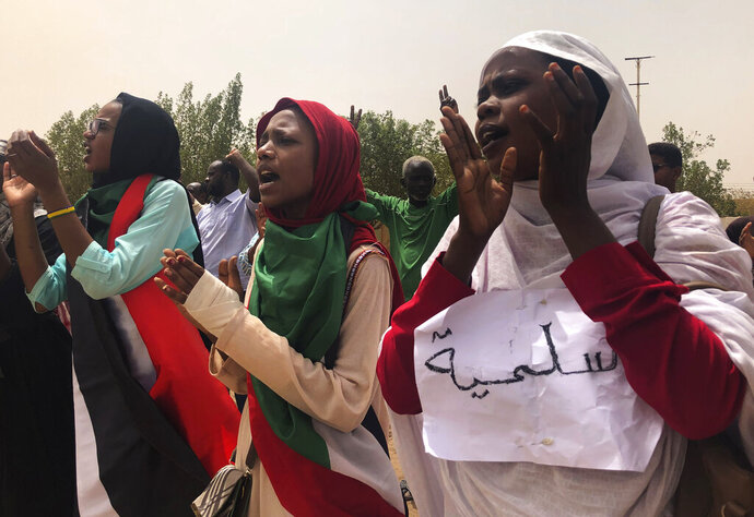Sudanese protesters shout slogans as they march during a demonstration against the ruling military council, in Khartoum, Sudan, Sunday, June 30, 2019. Tens of thousands of protesters have taken to the streets in Sudan's capital and elsewhere in the country calling for civilian rule nearly three months after the army forced out long-ruling autocrat Omar al-Bashir. The Arabic sign reads: