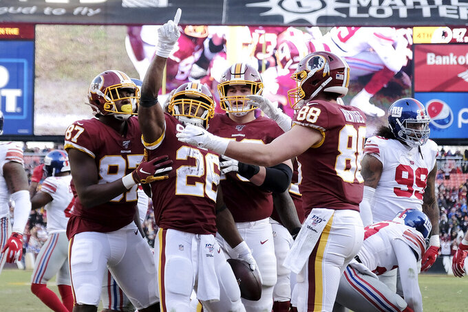 Washington Redskins running back Adrian Peterson (26) celebrates his touchdown run with teammates during the second half of an NFL football game against the New York Giants, Sunday, Dec. 22, 2019, in Landover, Md. (AP Photo/Mark Tenally)