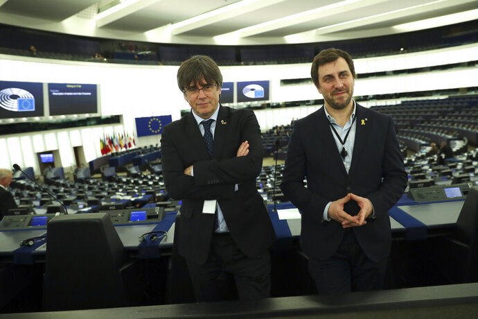 Catalonia's former regional president Carles Puigdemont, left, and former Catalan regional minister Antoni Comin stand in the plenary hemicycle of the European Parliament in Strasbourg, eastern France, Monday, Jan. 13, 2020. Puigdemont will attend his first session as a member of the European Parliament despite facing an arrest warrant against him in Spain. (AP Photo/Francisco Seco)