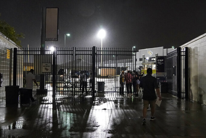 Fans gather near an entrance gate to the stadium during a lightning weather delay before an NCAA college football game between Central Florida and Boise State, Thursday, Sept. 2, 2021, in Orlando, Fla. (AP Photo/John Raoux)