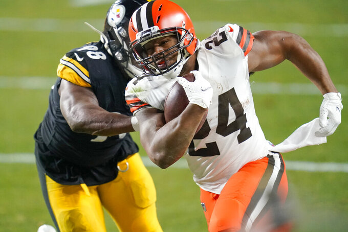 Cleveland Browns running back Nick Chubb (24) runs past Pittsburgh Steelers inside linebacker Vince Williams (98) during the first half of an NFL wild-card playoff football game, Sunday, Jan. 10, 2021, in Pittsburgh. (AP Photo/Keith Srakocic)