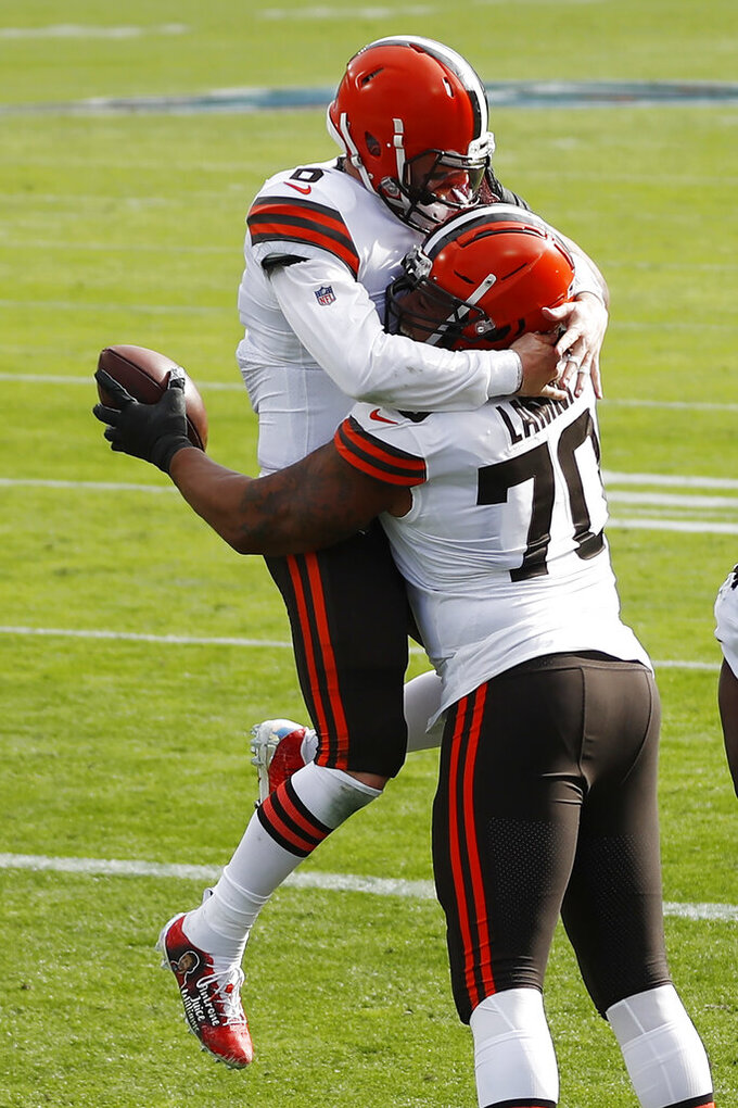 Cleveland Browns offensive tackle Kendall Lamm (70) celebrates with quarterback Baker Mayfield (6) after Lamm caught a touchdown pass against the Tennessee Titans in the first half of an NFL football game Sunday, Dec. 6, 2020, in Nashville, Tenn. (AP Photo/Wade Payne)