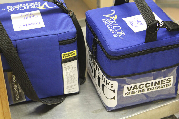 In this photo provided by Norton Sound Health Corp., are coolers containing Pfizer COVID-19 vaccines for the rural Alaska communities of Savoonga and Gambell being weighed at an air terminal in Nome, Alaska, on Jan. 14, 2021. Some of Alaska's highest vaccination rates among those 16 or older have been in some of its remotest, hardest-to-access communities, where the toll of past flu or tuberculosis outbreaks hasn't been forgotten. (Reba Lean/Norton Sound Health Corp. via AP)
