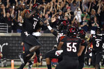 Louisville quarterback Jawon Pass (4) celebrates with teammates following his touchdown run during the first half of an NCAA college football game against Nitre Dame in Louisville, Ky., Monday, Sept. 2, 2019. (AP Photo/Timothy D. Easley)