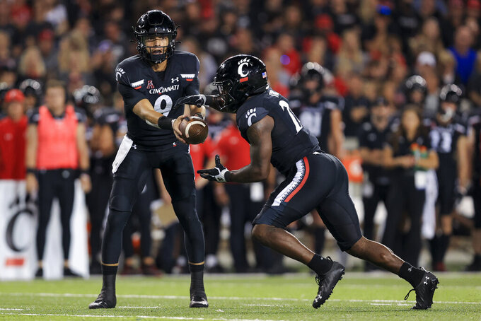 Cincinnati quarterback Desmond Ridder, left, hands off the ball to running back Jerome Ford during the second half of an NCAA college football game against Temple, Friday, Oct. 8, 2021, in Cincinnati. (AP Photo/Aaron Doster)
