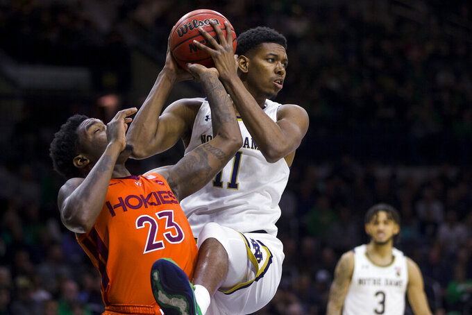 Notre Dame's Juwan Durham (11) grabs a rebound over Virginia Tech's Tyrece Radford (23) during the first half of an NCAA college basketball game Saturday, March 7, 2020, in South Bend, Ind. (AP Photo/Robert Franklin)