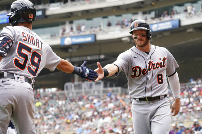 Detroit Tigers' Robbie Grossman (8) is greeted by Zack Short after Grossman scored on a two-run double by Jeimer Candelario off Minnesota Twins pitcher J.A. Happ in the fourth inning of a baseball game, Wednesday, July 28, 2021, in Minneapolis. (AP Photo/Jim Mone)
