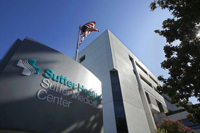 FILE - In this Sept. 20, 2019, file photo, an American flag flutters in the breeze outside of the Sutter Medical Center in Sacramento, Calif. Sutter Health has agreed to pay more than $30 million to the federal government to settle a lawsuit that accused it of paying doctors in exchange for patient referrals. The Sacrament Bee reports the agreement settles a 2014 secret lawsuit and was filed by the federal government and Laurie Hanvey, a whistleblower who once worked for Sutter as its compliance officer. The suit remained sealed until Thursday, Nov. 14, 2019. (AP Photo/Rich Pedroncelli, File)