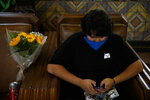 Miguel Gomez, 20, waits for a train next to his flowers at Union Station in Los Angeles, Monday, July 6, 2020. The coronavirus is blamed for over a half-million deaths worldwide, including more than 130,000 in the U.S., according to the tally kept by Johns Hopkins University. (AP Photo/Jae C. Hong)