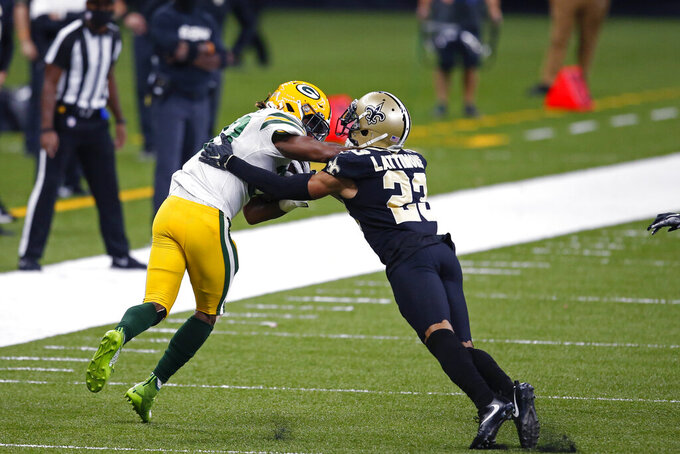 Green Bay Packers running back Aaron Jones carries against New Orleans Saints cornerback Marshon Lattimore (23) in the first half of an NFL football game in New Orleans, Sunday, Sept. 27, 2020. (AP Photo/Butch Dill)