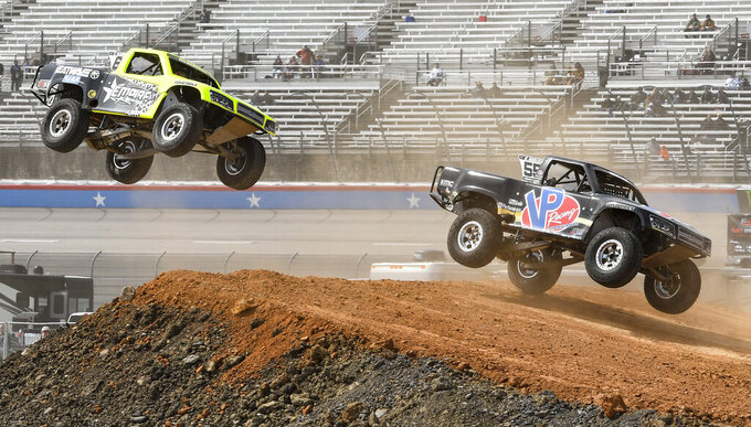 Blade Hildebrand, left, and Gavin Harlien, right, land a jump attempt during the Outdoor Powersports Offroad Rumble SST Race prior to a NASCAR Cup auto race at Texas Motor Speedway, Sunday, March 31, 2019, in Fort Worth, Texas. (AP Photo/Larry Papke)