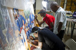 In this May 28, 2019 photo, Haitian artist Ernst Jeudy, left, helps to restore a painting by Haitian artist Edouard Duval Carrie, along with Franck Louissaint, center, Marc Gerard Estime, at the Musée d'Art du Collège Saint Pierre, in Port-au-Prince, Haiti.
