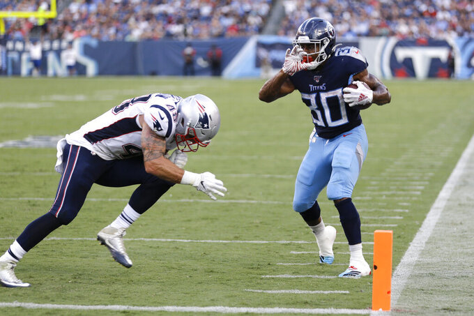 Tennessee Titans running back Jeremy McNichols (30) scores a touchdown as he is defended by New England Patriots linebacker Calvin Munson (48) in the first half of a preseason NFL football game Saturday, Aug. 17, 2019, in Nashville, Tenn. (AP Photo/James Kenney)