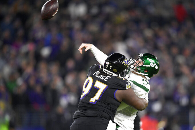 New York Jets quarterback Sam Darnold, right, tries to make a pass while taking a hit from Baltimore Ravens defensive tackle Michael Pierce (97) during the first half of an NFL football game, Thursday, Dec. 12, 2019, in Baltimore. (AP Photo/Nick Wass)