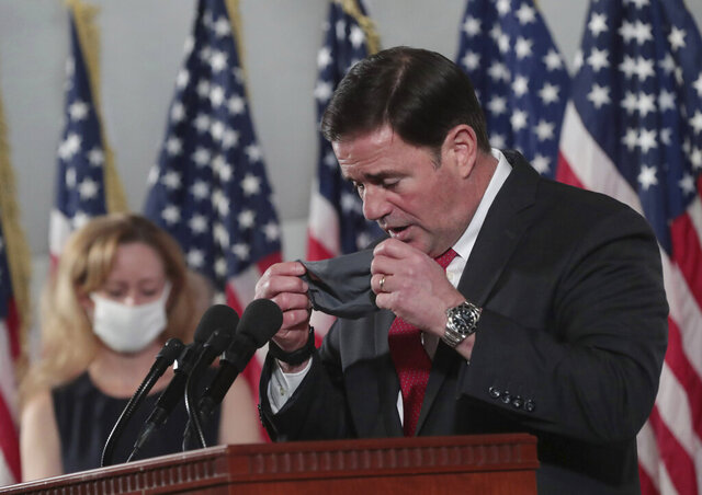FILE - In this Nov. 18, 2020, file photo, Arizona Gov. Doug Ducey puts his face mask on after addressing the media on COVID-19 during a news conference in Phoenix. Ducey has funneled nearly $400 million of federal coronavirus relief funds to state agencies to help pay for operations, allowing them to return some of their original budget allocations to the state treasury. (Michael Chow/The Arizona Republic via AP, File)