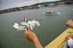A mourner holds orchids on Margaret Bridge across River Danube during the funeral ceremony of the two Hungarian victims of the boat accident las May in Budapest, Hungary, Friday, July 12, 2019. They were the two crew members of a tourist boat carrying 33 South Korean tourists that was crashed by a large river cruise ship and sank in River Danube at a pier of Margaret Bridge on May 29, killing 28 people. Seven Korean tourists survived the accident. (Marton Monus/MTI via AP)
