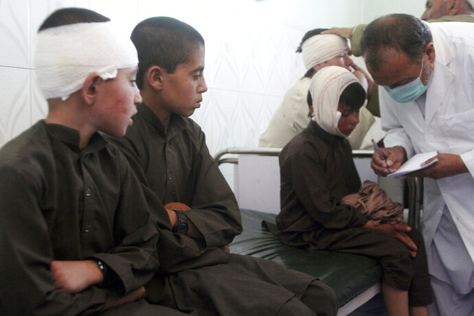 Injured boys receive treatment in a hospital after a car bomb attack in Ghazni province, central Afghanistan, Sunday, July 7, 2019. Afghan officials say a car bomb in central Afghanistan has killed a few people and wounded dozens of people, many of them students attending a nearby school. (AP Photo/Rahmatullah Nikzad)