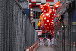 A large balloon appears through a narrow passageway from a street adjacent to the parade route during the modified Macy's Thanksgiving Day Parade in New York, Thursday, Nov. 26, 2020. Due to the pandemic, crowds of onlookers were not allowed to attend the annual parade. (AP Photo/Craig Ruttle)