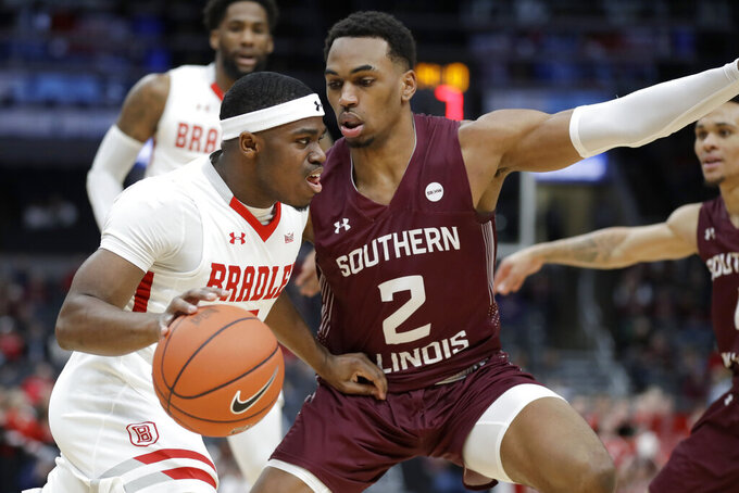 Bradley's Darrell Brown Jr., left, dribbles past Southern Illinois' Karrington Davis (2) during the first half of an NCAA college basketball game in the quarterfinal round of the Missouri Valley Conference men's tournament Friday, March 6, 2020, in St. Louis. (AP Photo/Jeff Roberson)