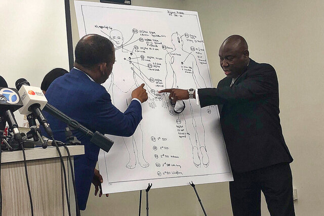 Attorneys Carl Douglas, left, and Benjamin Crump, right, point to bullet wounds on a diagram of Dijon Kizzee's body as part of an independent autopsy during a news conference in Los Angeles on Tuesday, Sept. 22, 2020. Dijon Kizzee, 29,