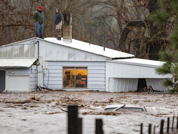 In this Thursday, Feb. 6, 2020 photo, Nate Fuller and Archie Morrow await rescue on the roof of a home in Thorn Hollow outside of Adams, Ore. The pair were stranded when they attempted to rescue the elderly couple who were stuck in the house as waters from the Umatilla River began to rise. All were rescued by helicopter that evening. Severe flooding in eastern Oregon closed a major freeway on Friday, forced evacuations in low-lying areas and stranded at least one family on their roof as other parts of the Pacific Northwest also braced for more flooding and landslides. (Ben Lonergan/East Oregonian via AP)