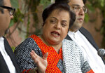 FILE - In this Wednesday, Nov. 27, 2013 file photo, Shireen Mazari, center, leader of the Pakistan Tehreek-e-Insaf party, addresses a news conference with party officials, in Islamabad, Pakistan. The government's Human Rights Minister Mazari said in a series of tweets.