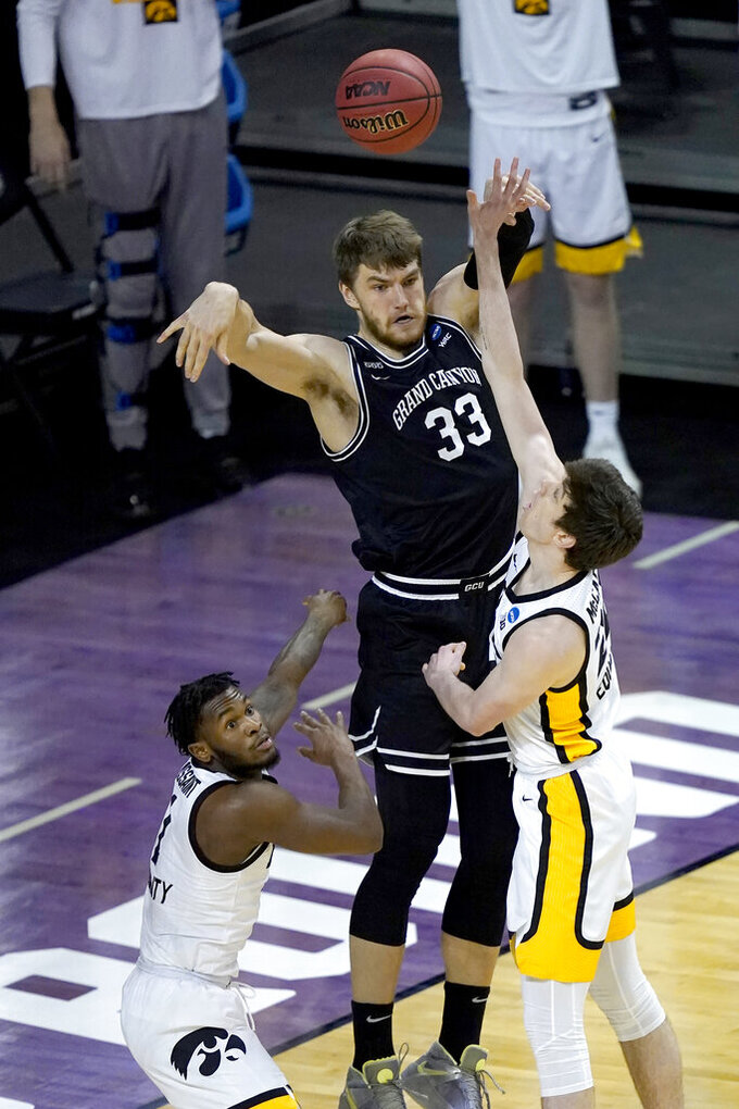 Grand Canyon's Asbjorn Midtgaard (33) passes under pressure from Iowa's Joe Toussaint, left and Patrick McCaffery during the first half of a first round NCAA college basketball tournament game Saturday, March 20, 2021, at the Indiana Farmers Coliseum in Indianapolis. (AP Photo/Charles Rex Arbogast)
