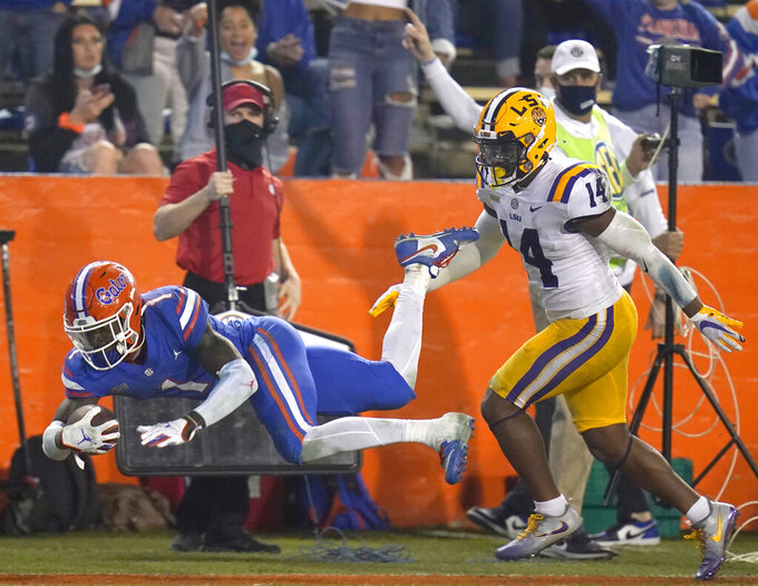 Florida wide receiver Kadarius Toney (1) is pushed out of bounds by LSU safety Maurice Hampton Jr. (14) after Toney caught a pass for a 49-yard gain during the second half of an NCAA college football game Saturday, Dec. 12, 2020, in Gainesville, Fla. (AP Photo/John Raoux)
