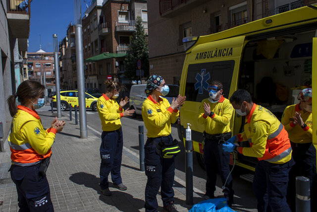Health personnel wearing protection gear to protect against the spread of the new coronavirus clean their hands after attending to a patient, in Barcelona, Spain, Monday, April 6, 2020. Spanish Prime Minister Pedro Sánchez Sánchez announced that he would ask the Parliament to extend the state of emergency by two more weeks, taking the lockdown on mobility until April 26. The new coronavirus causes mild or moderate symptoms for most people, but for some, especially older adults and people with existing health problems, it can cause more severe illness or death. (AP Photo/Emilio Morenatti)