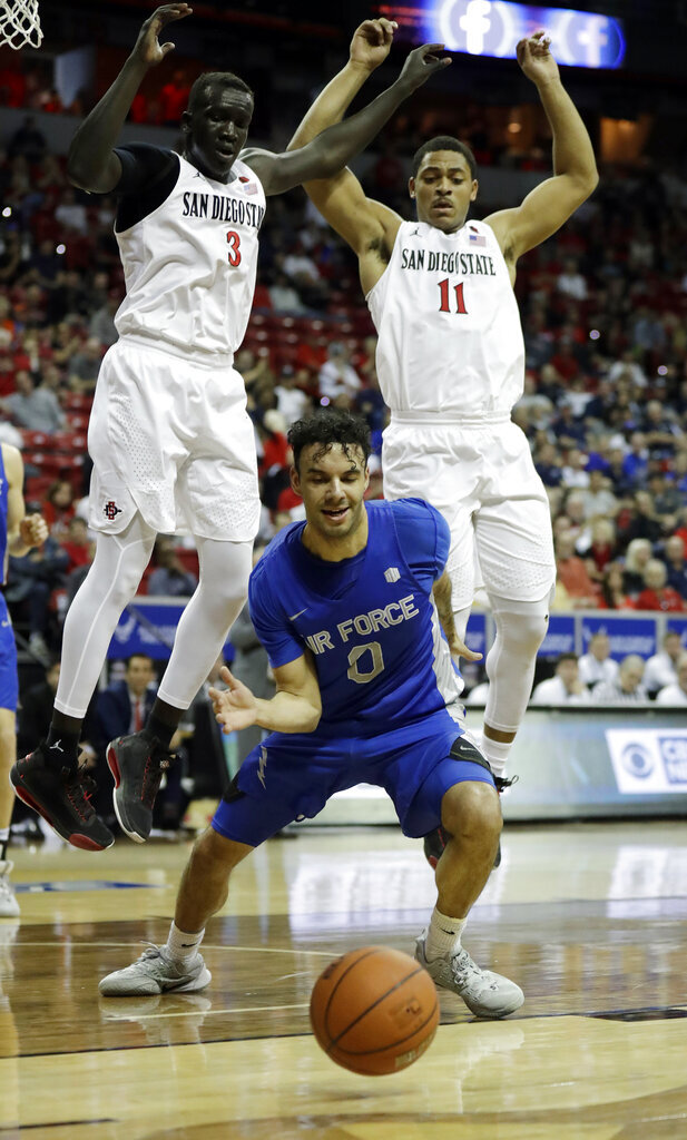 Air Force's Caleb Morris (0) reaches for a loose ball as San Diego State's Aguek Arop (3) and Matt Mitchell (11) defend during the first half of a Mountain West Conference tournament NCAA college basketball game Thursday, March 5, 2020, in Las Vegas. (AP Photo/Isaac Brekken)
