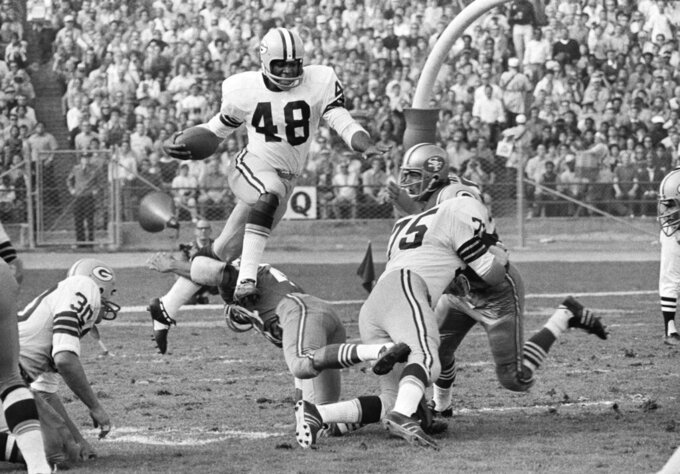 "File- This Nov. 2, 1970. file photo shows Green Bay Packer cornerback Ken Ellis (48) leaping as he returns a 49er punt in third quarter NFL action in San Francisco. Packer guard at right is Forrest Gregg (75).  ""It's going to be a long time, another 100 years, before somebody wins himself six titles,"" said  Herb Adderley, the Hall of Fame cornerback for Vince Lombardi's great Green Bay Packers teams of the 1960s. Adderley, who turns 80 next month, won five championships in Green Bay, including the first two Super Bowls, plus another with Tom Landry's Dallas Cowboys in 1971, as did Forrest Gregg, who died last month at age 85. (AP Photo/File)"