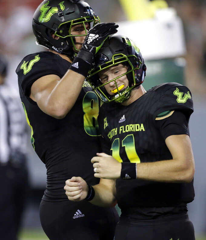South Florida quarterback Blake Barnett, right, celebrates with tight end Mitchell Wilcox after scoring on a 20-yard run during the second half of an NCAA college football game against Connecticut, Saturday, Oct. 20, 2018, in Tampa, Fla. (AP Photo/Chris O'Meara)