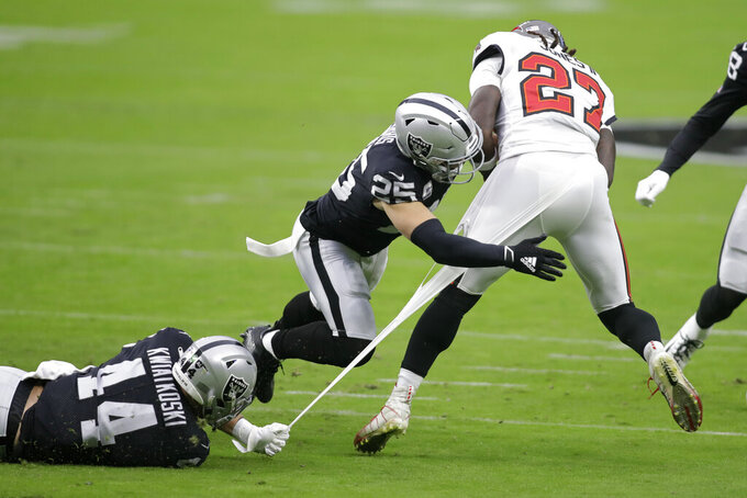 Las Vegas Raiders inside linebacker Nick Kwiatkoski (44) and free safety Erik Harris (25) attempt to tackle Tampa Bay Buccaneers running back Ronald Jones (27) during the first half of an NFL football game, Sunday, Oct. 25, 2020, in Las Vegas. (AP Photo/Isaac Brekken)