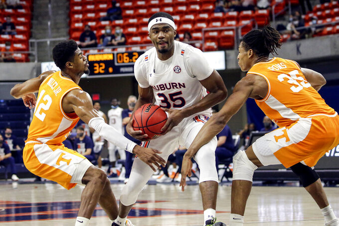 Auburn guard Devan Cambridge (35) tries to drive to the basket between Tennessee guard Victor Bailey Jr. (12) and Tennessee guard Yves Pons (35) during the first half of an NCAA basketball game Saturday, Feb. 27, 2021, in Auburn, Ala. (AP Photo/Butch Dill)