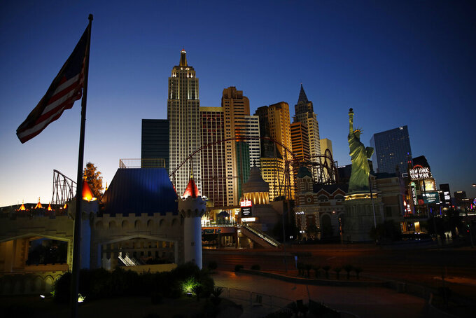 FILE - In this April 28, 2020, file photo, the sun sets behind casinos and hotels along the Las Vegas Strip in Las Vegas. Unions representing 65,000 Las Vegas-area casino workers are suing some resort operators, alleging that employees are being put at risk of illness and death due to skimpy safety measures during the coronavirus pandemic. A lawsuit filed Monday, June 29, 2020, in U.S. District Court in Las Vegas does not directly cite the death last week of Adolfo Fernandez, a 51-year-old Caesars Palace porter and union member who was diagnosed with the COVID-19 respiratory illness after returning to work when casinos reopened June 4. (AP Photo/John Locher, File)