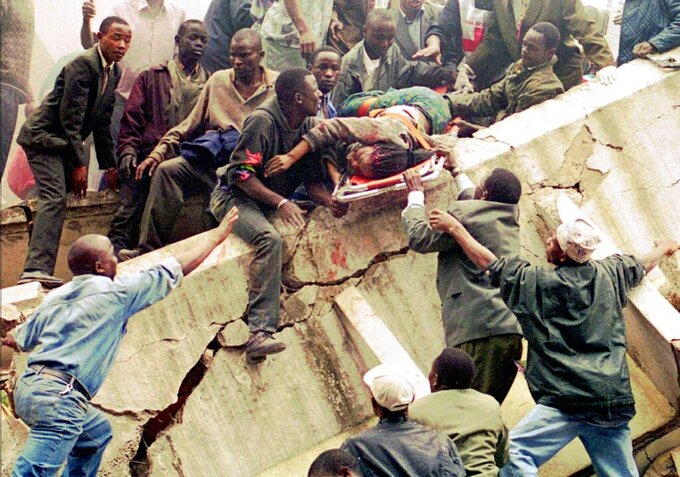 FILE - In this Friday, Aug. 7, 1998 file photo, rescue workers carry Susan Francisca Murianki, a U.S. embassy office worker, over the rubble of a collapsed building next to the embassy, in Nairobi, Kenya. In 1996, Osama bin Laden issued a formal declaration of war. But it wasn't until trucks loaded with explosives detonated outside of U.S. embassies in Nairobi and Dar es Salaam, Tanzania, killing more than 200 people on Aug. 7, 1998, that the threat became real. (AP Photo/Khalil Senosi, File)