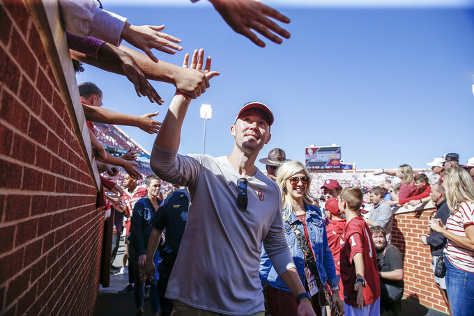 Oklahoma head coach Lincoln Riley high-fives fans following an NCAA college football game against West Virginia in Norman, Okla., Saturday, Oct. 19, 2019. Oklahoma won 52-14. (AP Photo/Alonzo Adams)