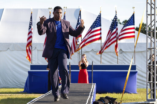 FILE -  Senate candidate Herschel Walker takes the stage during former president Donald Trump's Save America rally in Perry, Ga., on Saturday, Sept. 25, 2021. Walker canceled a planned Texas fundraiser on Wednesday, Oct. 13 because an organizer was displaying a swastika made from syringes on social medial to protest mandatory vaccination.  (AP Photo/Ben Gray, File)