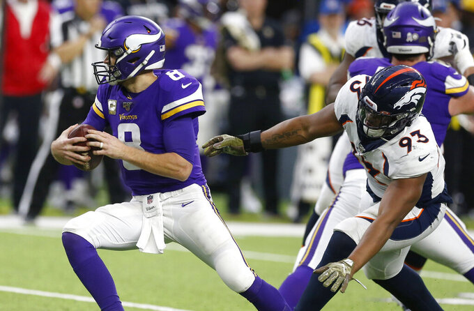 Minnesota Vikings quarterback Kirk Cousins, left, runs from Denver Broncos defensive end Dre'Mont Jones, right, during the second half of an NFL football game, Sunday, Nov. 17, 2019, in Minneapolis. (AP Photo/Jim Mone)